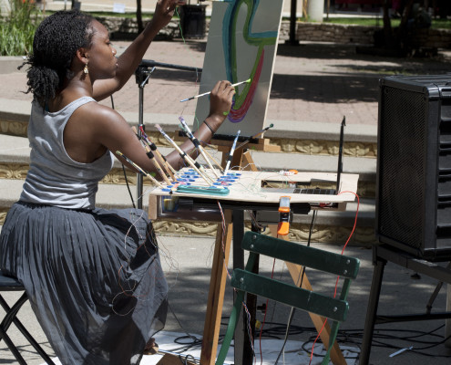Camry Ivory playing two chords at once through the use of her paint brushes. Photo by Madison Kludy