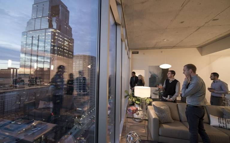 Sean Ray (foreground) and R.J. Stebbins (to the left of Ray) admired the view of downtown from one of the penthouses on the 26th floor during a party Tuesday to officially open the One Light apartment building. Ray and Stebbins will become roommates in One Light next month.